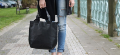 Ripped jeans, black coat.